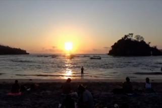 Menikmati matahari terbenam di  pantai berair bening
